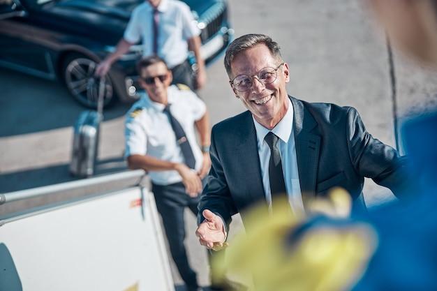 Bovenaanzicht taille portret van gelukkige zakenman die de trap op loopt terwijl hij wordt begroet door gastvrij personeel