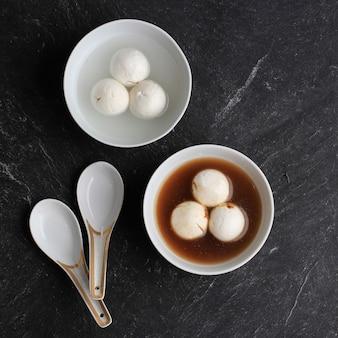 Bovenaanzicht tang yuan (wedang ronde), chinese kleefrijst knoedelballen met suikergember of palmsuikersiroop op rood chinees op zwarte achtergrond voor winterzonnewende nieuwjaarsfestivalvoedsel.