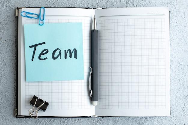 Bovenaanzicht team geschreven nota met blocnote en pen op witte achtergrond job office school college business copybook kleur
