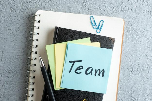 Bovenaanzicht team geschreven nota over stickers met blocnote en pen op witte achtergrond kleur baan kantoor school voorbeeldenboek college zaken