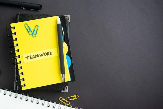 Bovenaanzicht teamwerk notitie met blocnotes op donkere achtergrond