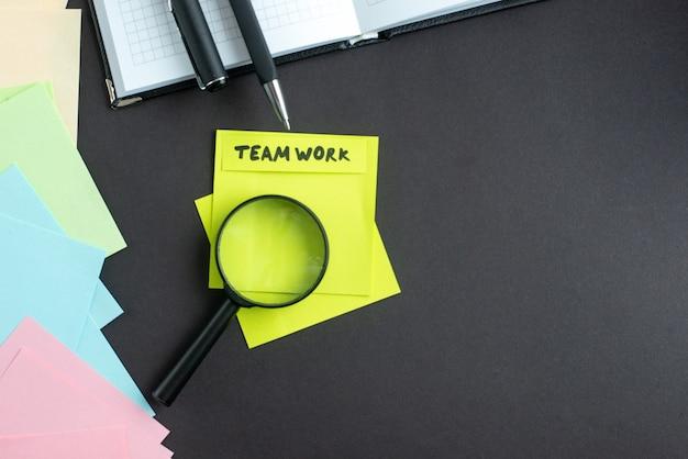 Bovenaanzicht teamwerk notitie met stickers pennen en vergrootglas op donkere achtergrond