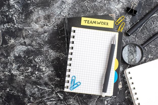 Bovenaanzicht teamwerknota gehecht aan zwarte blocnote op een donkere achtergrond