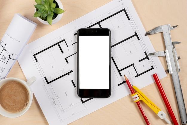 Bovenaanzicht telefoon bovenop architecturaal plan
