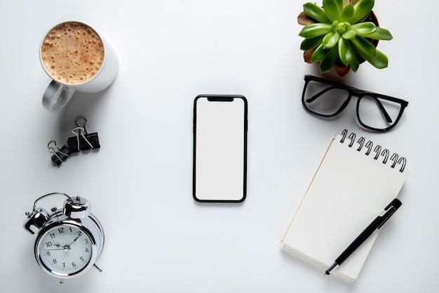 Bovenaanzicht telefoon op bureau met kladblok