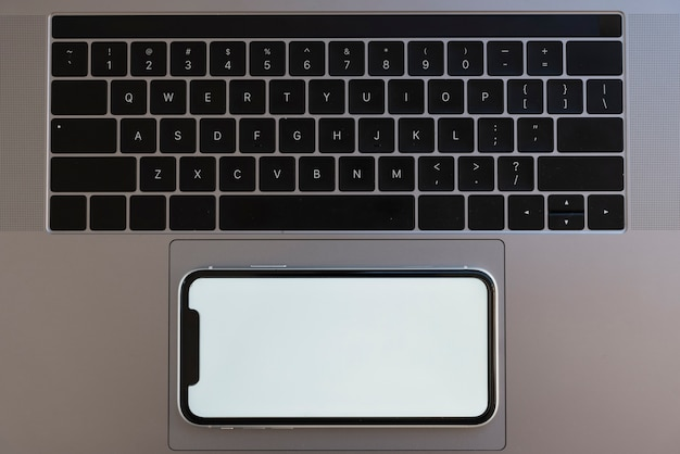 Bovenaanzicht telefoon op laptop touchpad
