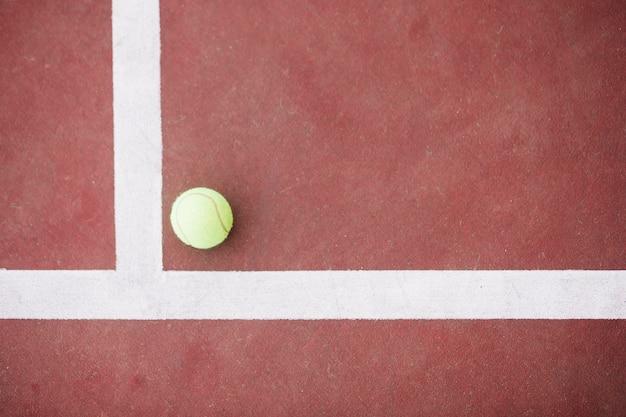 Bovenaanzicht tennisbal op hoek op veld