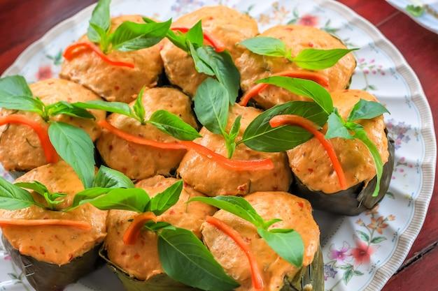 Bovenaanzicht thaise gestoomde curry vis in bananenblad kopjes gedecoreerd met basilicumblad, (hor mok pla)