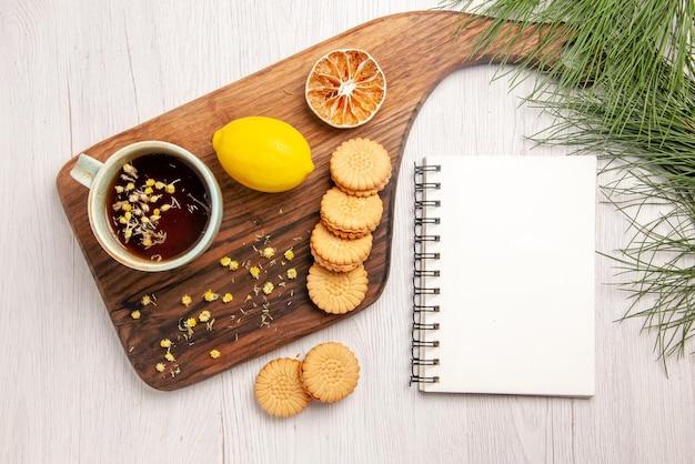Bovenaanzicht thee en citroen een kopje thee met kruidenkoekjes en citroen op het witte notitieboekje van het keukenbord en kerstboomtakken
