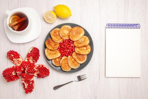 Bovenaanzicht thee en pannenkoeken een kopje thee met kaneel en citroen gepelde granaatappel citroen naast de witte notebook plaat van zaden van rode granaatappel en pannenkoeken en vork op de witte achtergrond