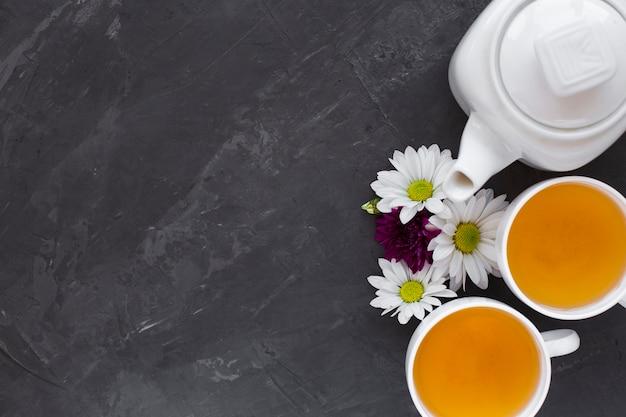 Bovenaanzicht thee kopjes en bloemen met kopie ruimte