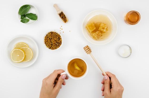 Bovenaanzicht thee met citroen en honing en stuifmeel