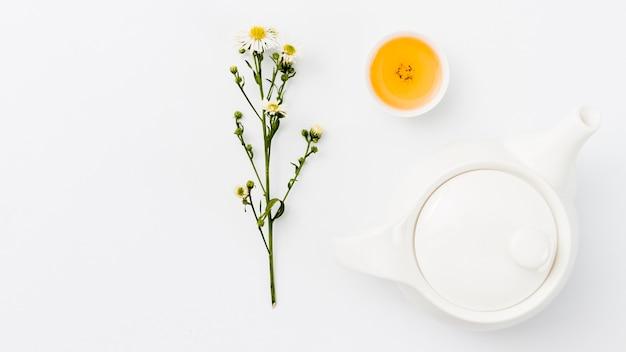 Bovenaanzicht theepot met beker en bloem
