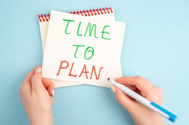 Bovenaanzicht tijd om te plannen geschreven op notitie in vrouwelijke handen op blauwe tafel