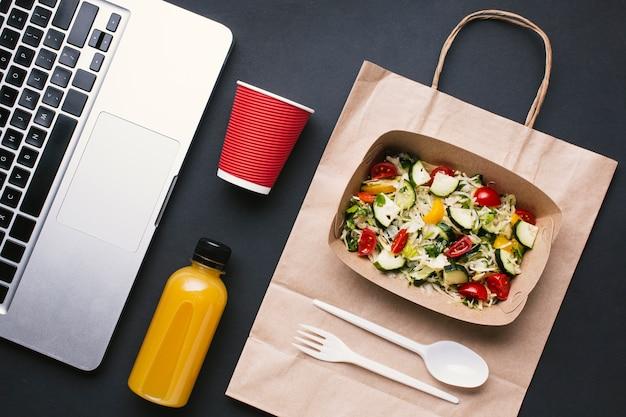 Bovenaanzicht toetsenbord en salade op zwarte achtergrond
