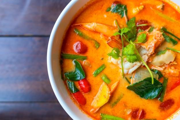 Bovenaanzicht tom yam kung pittige thaise soep met garnalen in witte kom op houten tafel.