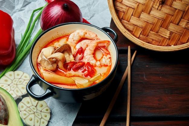 Bovenaanzicht tom yam met garnalen, zeevruchten, kokosmelk en spaanse peper in compositie met ingrediënten. populaire hete en zure thaise soep. kopieer ruimte. tom yum