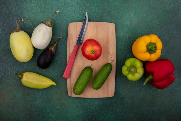 Bovenaanzicht tomaat met komkommers op een snijplank met een mes en gekleurde paprika aubergines op een groene achtergrond