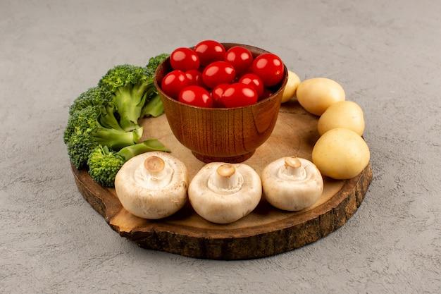 Bovenaanzicht tomaten champignons broccoli vers rijp op het bruine bureau en grijze vloer