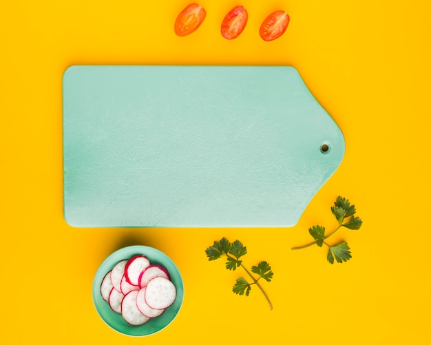 Bovenaanzicht tomaten en radijs plakjes met snijplank kopie-ruimte