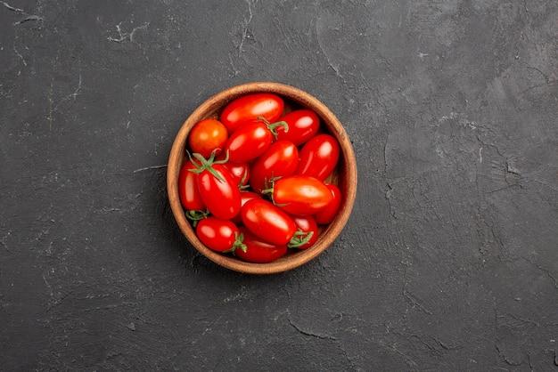 Bovenaanzicht tomaten in kom rijpe rode tomaten in kom in het midden van de donkere tafel