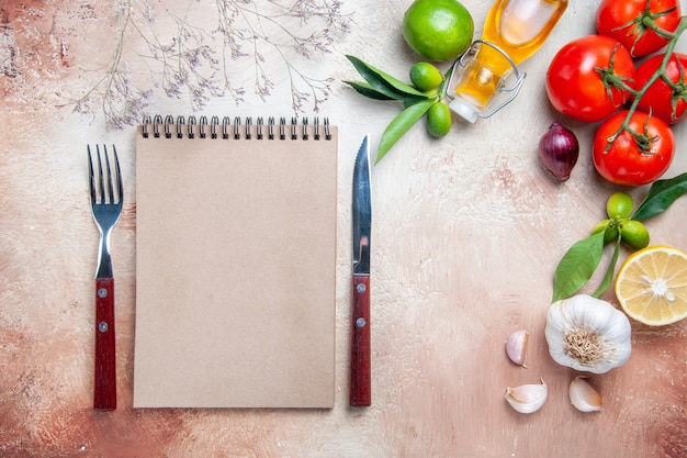 Bovenaanzicht tomaten tomaten knoflook fles olie citroen bladeren crème notebook mes vork