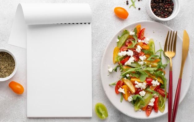 Bovenaanzicht tomatenmix salade met fetakaas en leeg notitieboekje