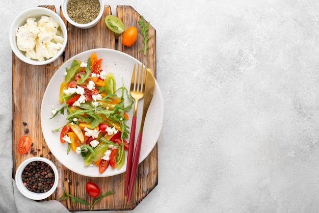 Bovenaanzicht tomatenmix salade met fetakaas, rucola en kopie-ruimte