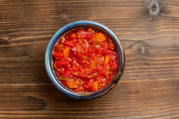 Bovenaanzicht tomatensaus met groenten op bruine achtergrond maaltijdsaus tomatengroente