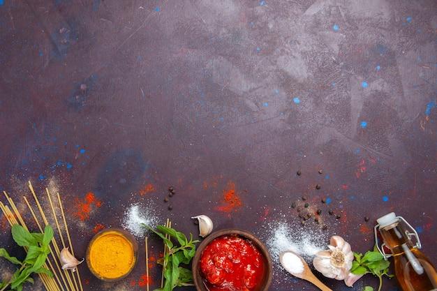 Bovenaanzicht tomatensaus met kruiden op donkere achtergrond pittige maaltijdvoedsel saus
