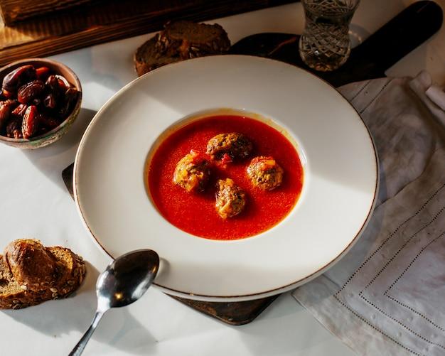 Bovenaanzicht tomatensoep met vleesrolletjes samen met sneetjes brood op het witte oppervlak
