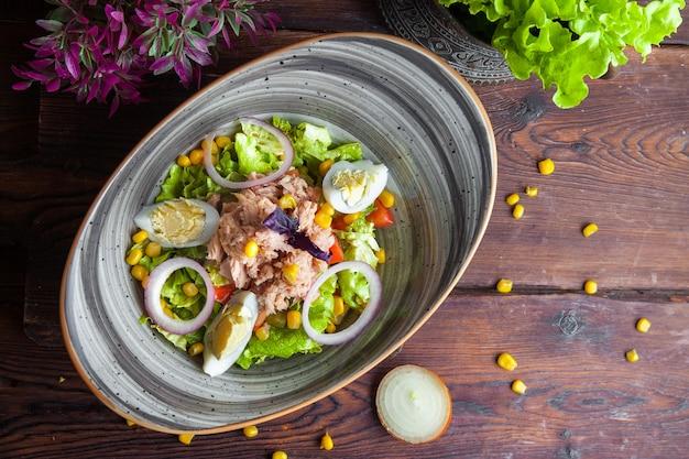 Bovenaanzicht tonijn vissalade met sla, tomaten, eieren, komkommer, ui en maïs op een donkere houten oppervlak horizontale