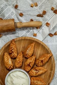 Bovenaanzicht traditionele azerbeidzjan schotel gebakken gyurza met yoghurt op een dienblad op een krant