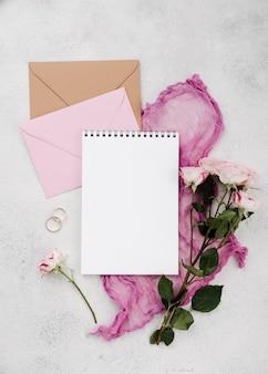 Bovenaanzicht trouwringen met bloemen en enveloppen