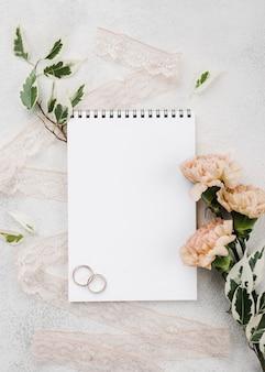 Bovenaanzicht trouwringen met bloemen op de tafel