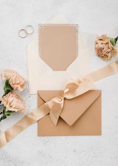 Bovenaanzicht trouwringen met lint en enveloppen