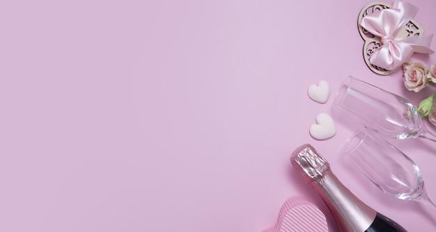 Bovenaanzicht twee glazen, champagne, bloemen op een roze achtergrond met kopie ruimte valentijnsdag datum concept