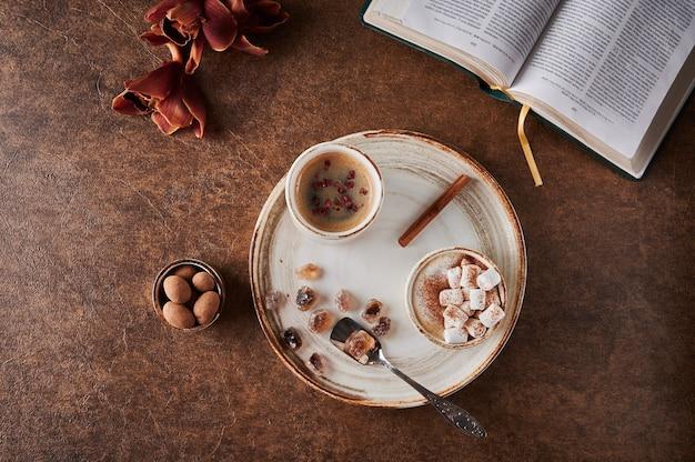 Bovenaanzicht twee kopjes koffie met schuim en marshmallow en gesublimeerde frambozen met kaneel erop