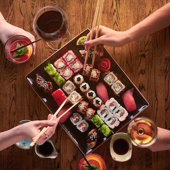 Bovenaanzicht. twee meisjes eten sushi. set van verschillende soorten broodjes en sushi met drankjes