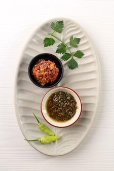 Bovenaanzicht twee verschillende indonesische sambal sambal ijo green chili paste en sambal bawang