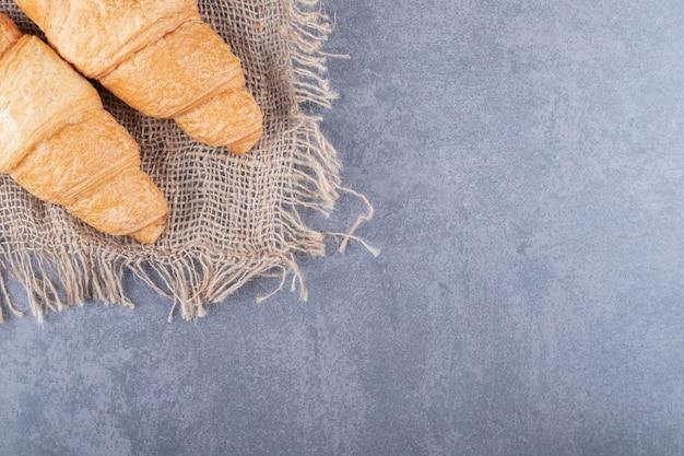 Bovenaanzicht twee verse franse croissants op zak over grijze achtergrond.