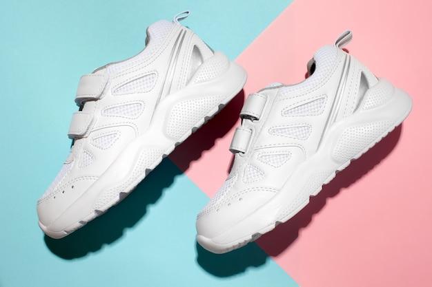 Bovenaanzicht twee witte nieuwe sneakers aan de zijkant met klittenband op een zacht pastel geometrisch papier p...