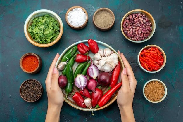 Bovenaanzicht uien en knoflook met greens en kruiden op de donkerblauwe tafelgroente voedselsalade-ingrediënten
