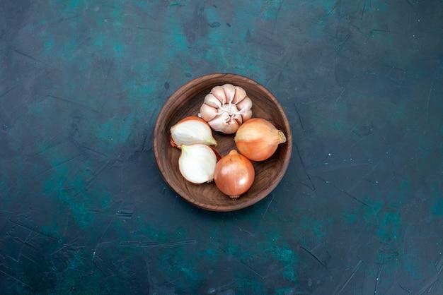 Bovenaanzicht uien en knoflook op blauw bureau