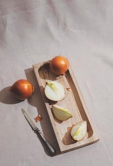Bovenaanzicht uien op een houten bord