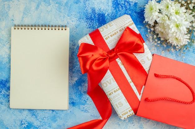 Bovenaanzicht vakantie cadeau met rood lint blocnote rode papieren zak bloemen op blauwe achtergrond