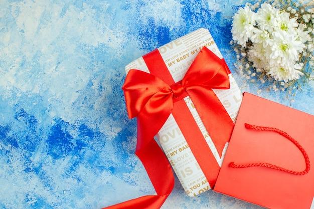 Bovenaanzicht vakantie cadeau met rood lint rode papieren zak bloemen op blauwe achtergrond met vrije ruimte