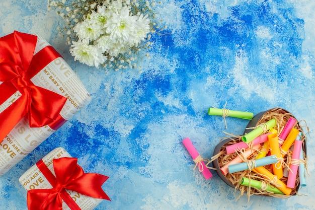 Bovenaanzicht vakantiegeschenken scroll wenspapieren in hartvormige doos op blauwe achtergrond vrije ruimte