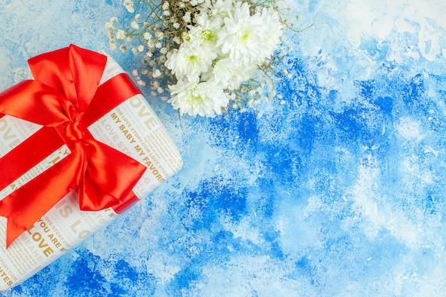 Bovenaanzicht vakantiegeschenken witte bloemen op blauwe achtergrond vrije ruimte