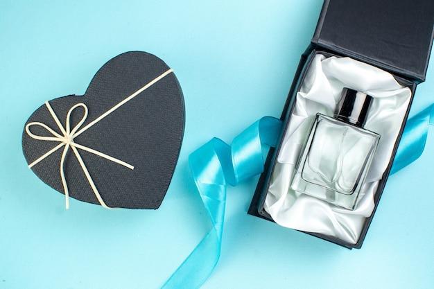 Bovenaanzicht valentijnsdag aanwezig parfum op blauw oppervlak liefde paar gevoel kleur huwelijk parfum cadeau vrouw Gratis Foto